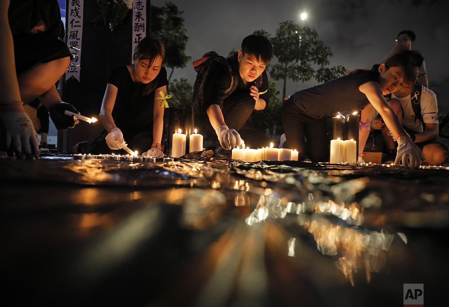 People light candles during a vigil to mourn the recent suicide of a woman due to the government's policy on an extradition bill, in Hong Kong, Saturday, July 6, 2019.  (AP Photo/Vincent Yu)