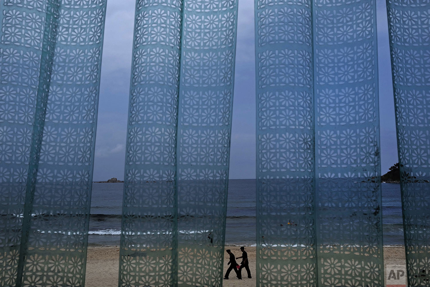 Two man walk at Sijung Ho beach against a plastic curtain outside a restaurant in North Korea, Sunday, July 14, 2019.  (AP Photo/Vincent Yu)