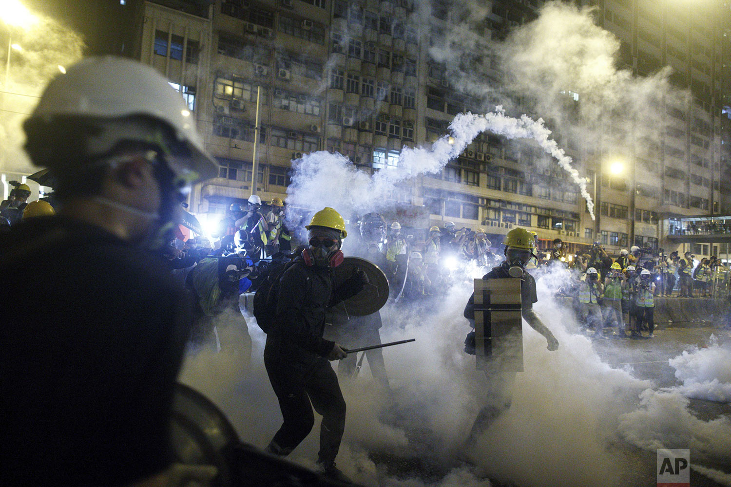 Protesters react to tear gas during a confrontation with riot police in Hong Kong, July 21, 2019.  (Eric Tsang/HK01 via AP)