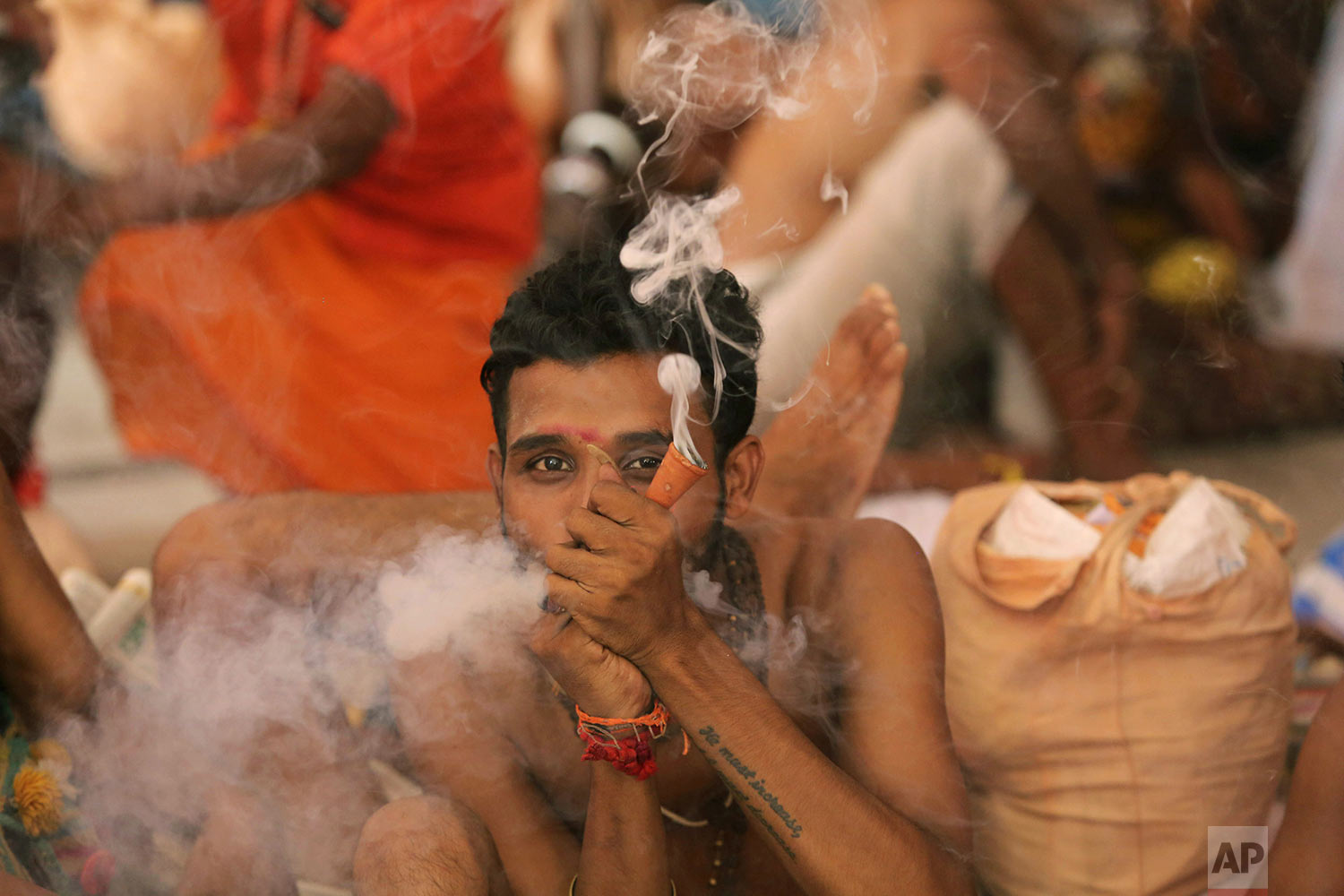 A Hindu holy man smokes as he waits to register for the annual pilgrimage to the Amarnath cave shrine in Jammu, India, July 1, 2019. (AP Photo/Channi Anand)