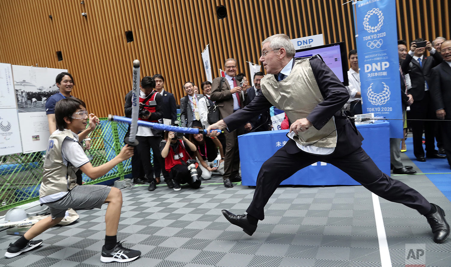 IOC President Thomas Bach, right, demonstrates fencing with Japanese junior high school student Yui Hashimoto during a Olympic Games Tokyo 2020 One year to Go ceremony event in Tokyo, July 24, 2019. (AP Photo/Koji Sasahara, Pool)