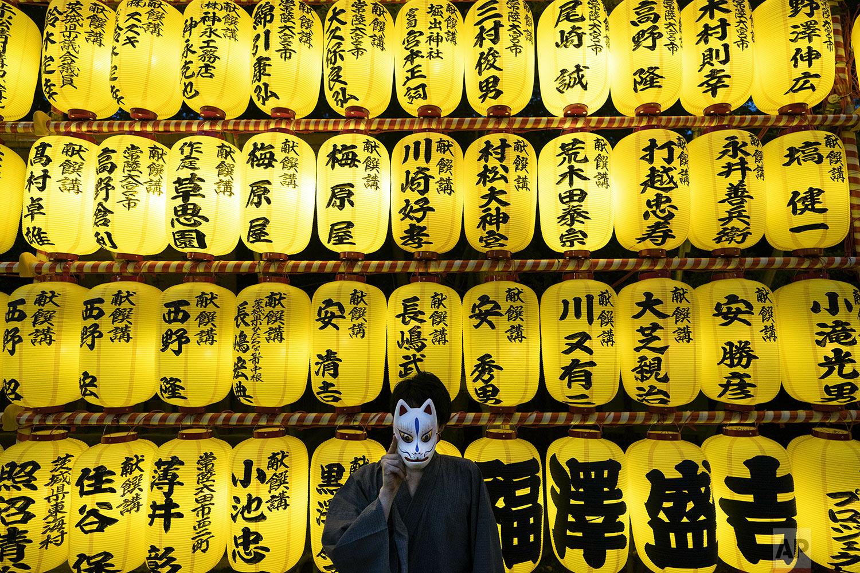A man wearing yukata (summer kimono) poses with a mask as thousands of lanterns are lit up during the Mitama festival at Yasukuni Shrine, in Tokyo, Saturday, July 13, 2019. (AP Photo/Jae C. Hong)
