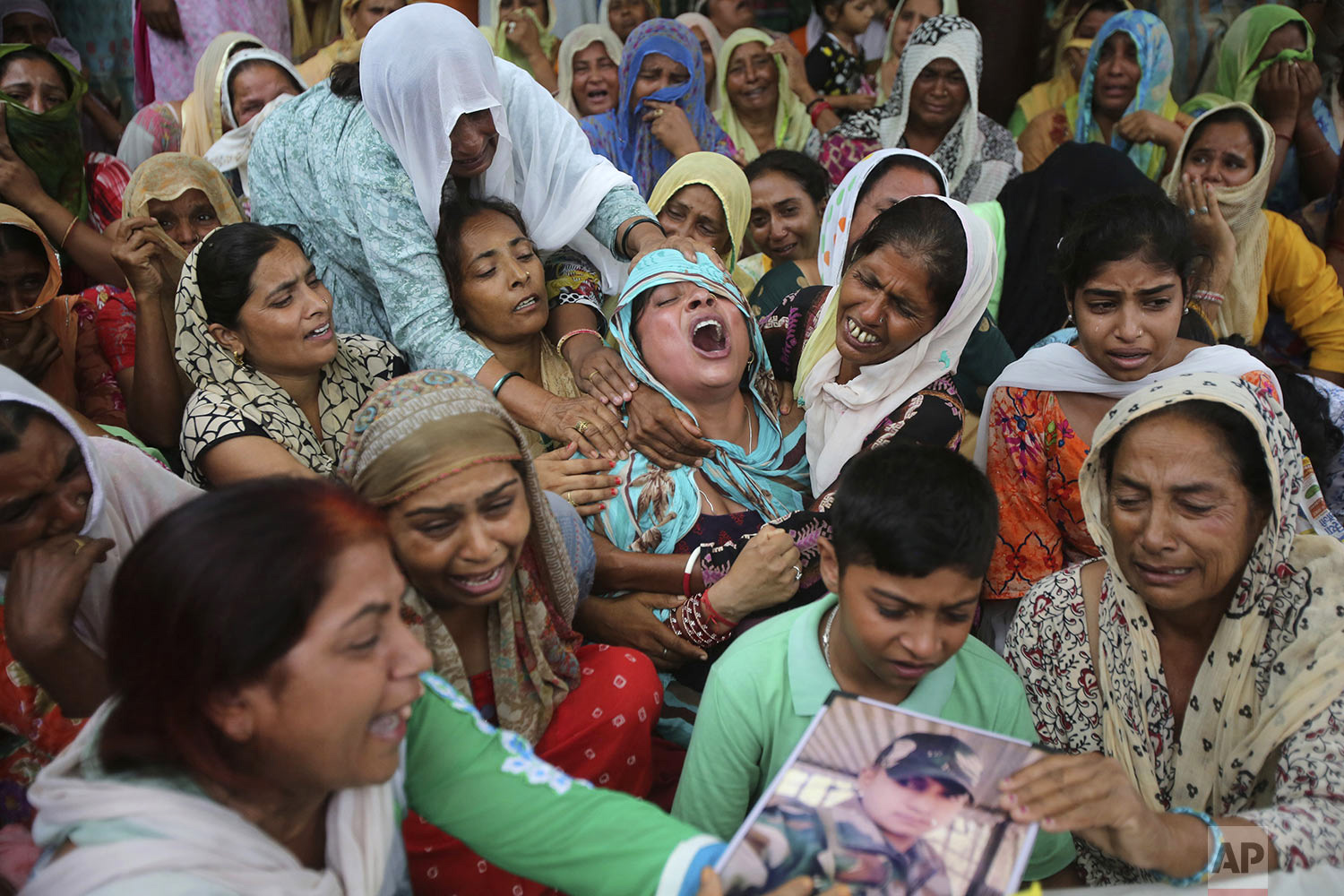 A woman, center, wails by the body of her husband,  Indian army soldier Krishan Lal, who was killed from shots fired from the Pakistan side of the border, at Ghagriyal village, in Akhnoor, about 62 kilometers (51 miles) from Jammu, India, July 31, 2019.  (AP Photo/Channi Anand)