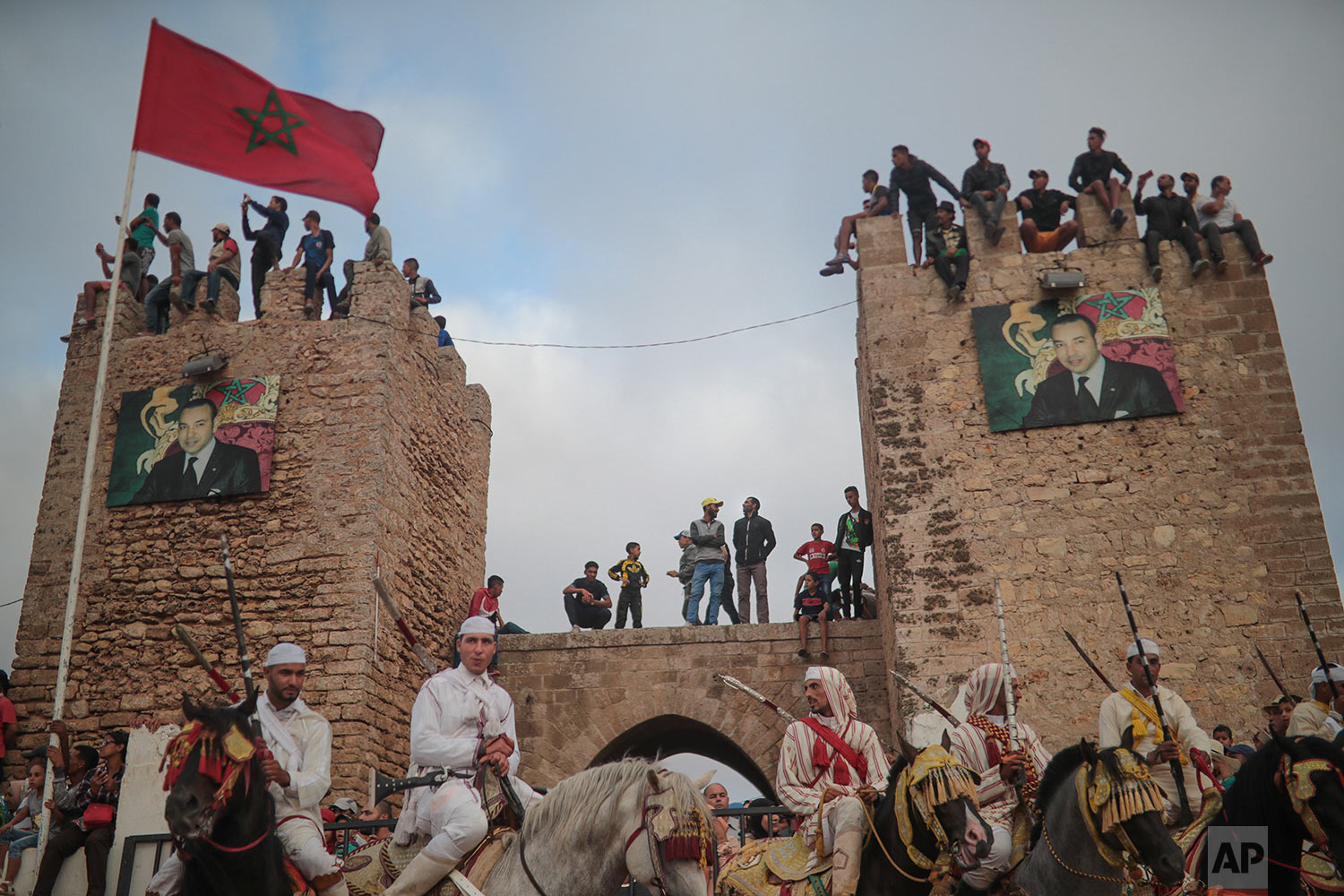 People watch atop an ancient wall as riders wait during Tabourida, a traditional horse riding show also known as Fantasia, in the coastal town of El Jadida, Morocco, July 25, 2019. (AP Photo/Mosa'ab Elshamy)