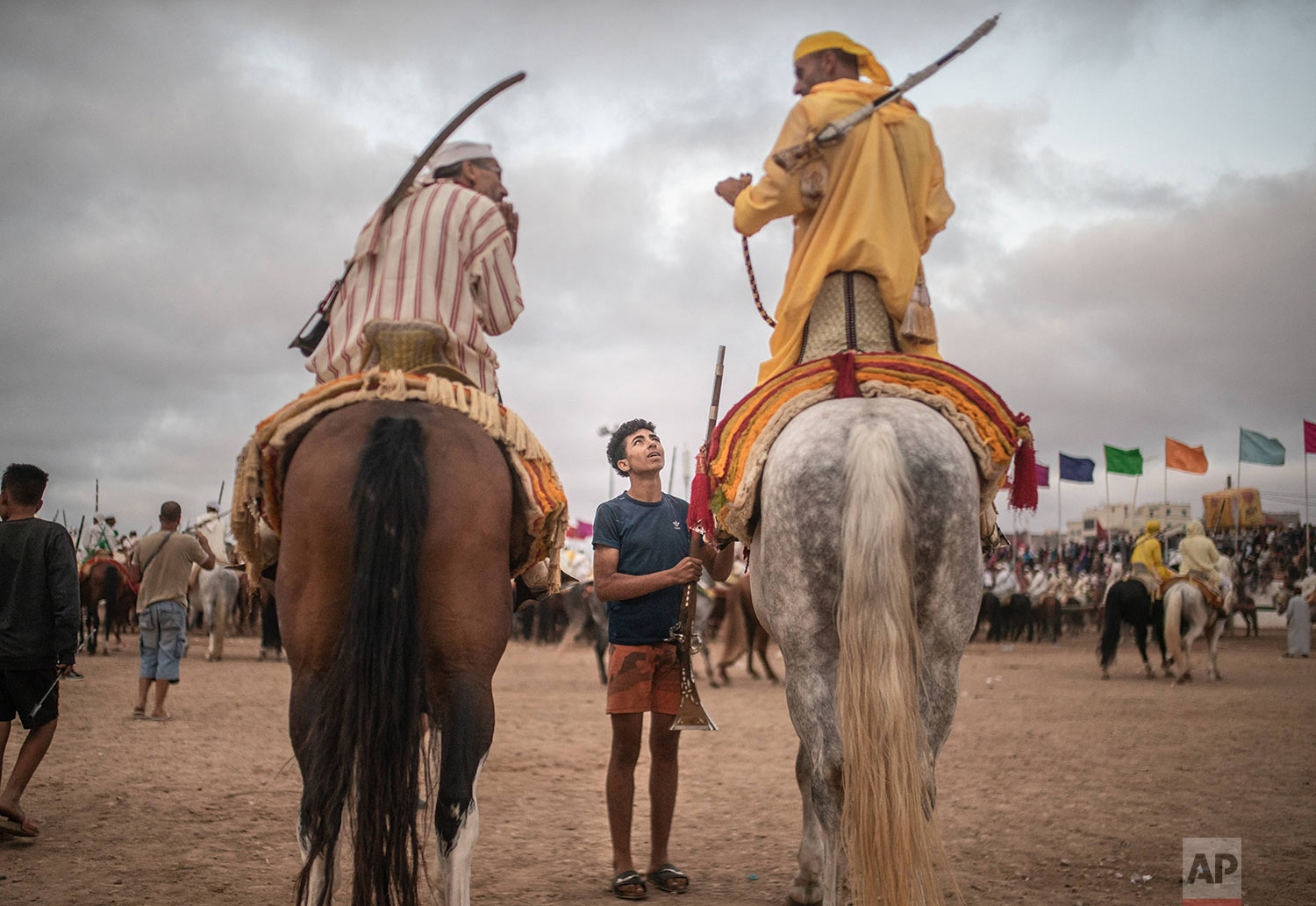 A boy hands a file to horse riders waiting for their turn to take part in an equestrian show known as Fantasia or Tabourida, in the coastal town of El Jadida, Morocco, July 25, 2019. (AP Photo/Mosa'ab Elshamy)