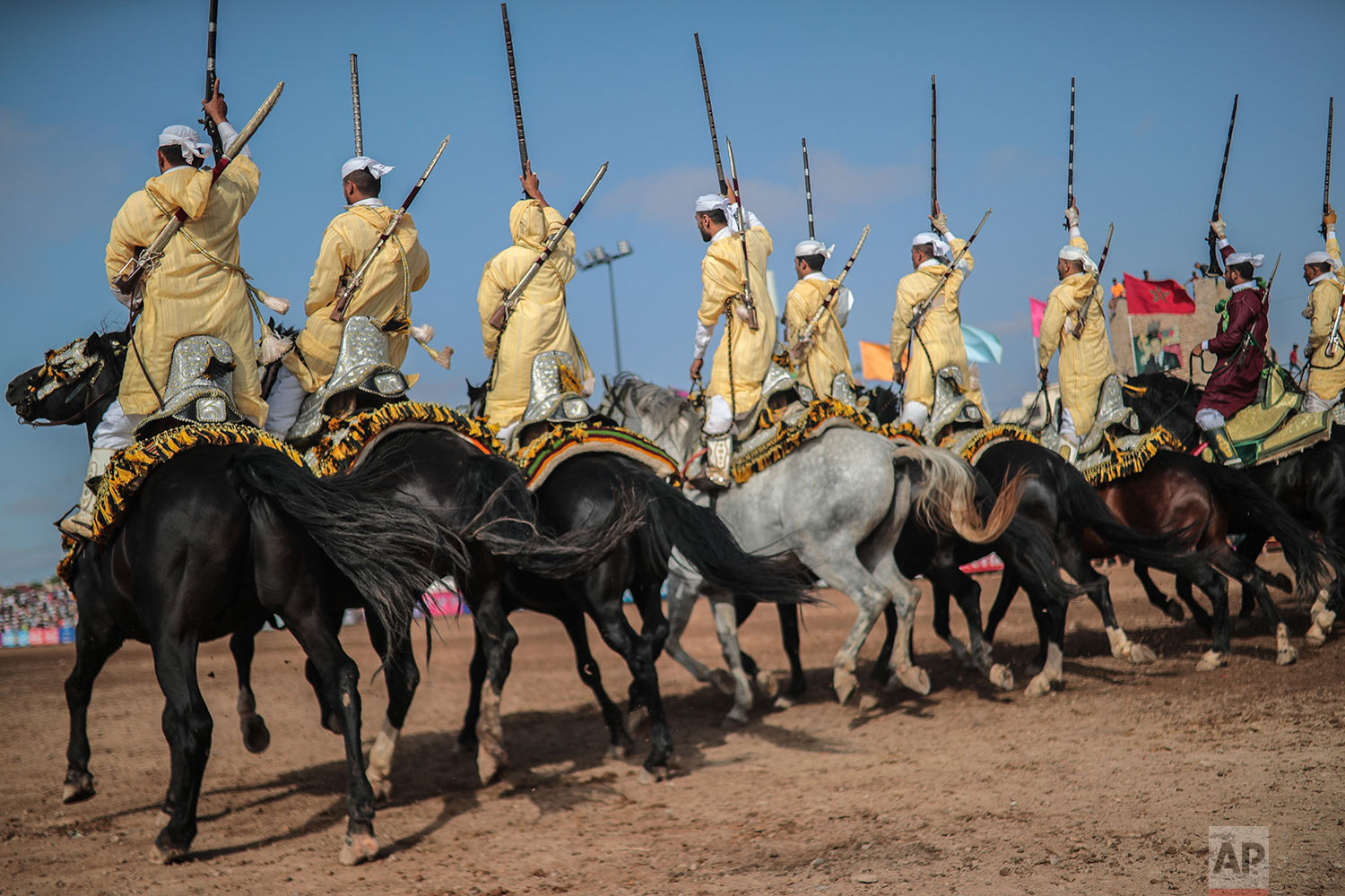 A troupe charges and hold their rifles before firing, during Tabourida, a traditional horse riding show also known as Fantasia, in the coastal town of El Jadida, Morocco, July 25, 2019. (AP Photo/Mosa'ab Elshamy)