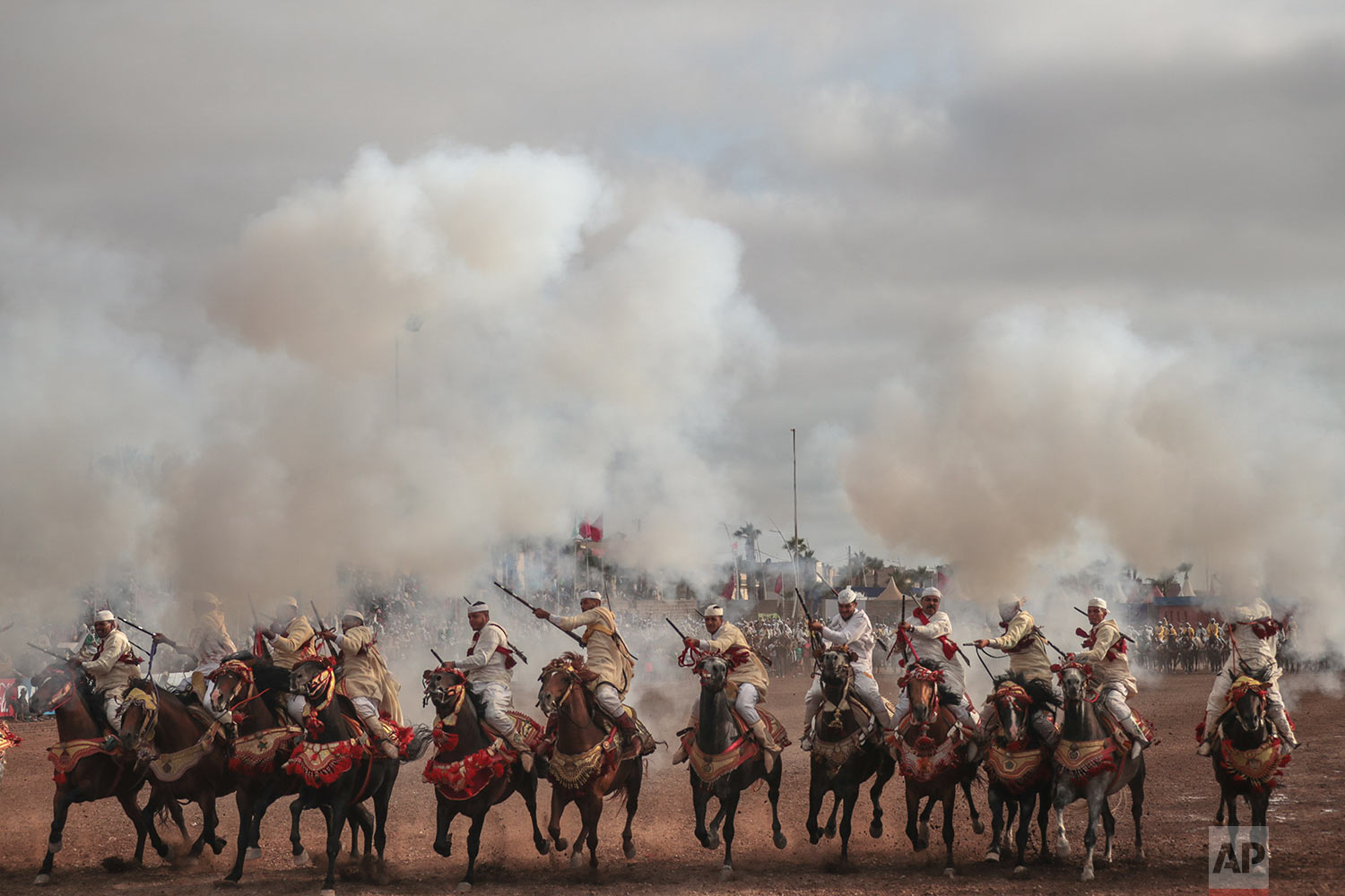 A troupe charges and fire their rifles during Tabourida, a traditional horse riding show also known as Fantasia, in the coastal town of El Jadida, Morocco, July 25, 2019. (AP Photo/Mosa'ab Elshamy)