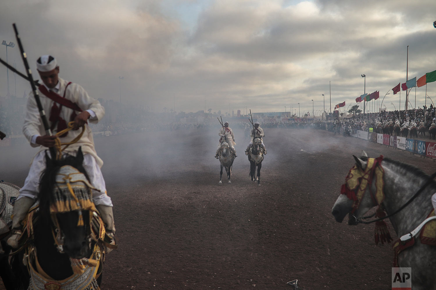 A troupe is engulfed by smoke after firing their rifles during Tabourida, a traditional horse riding show also known as Fantasia, in the coastal town of El Jadida, Morocco, July 25, 2019. (AP Photo/Mosa'ab Elshamy)