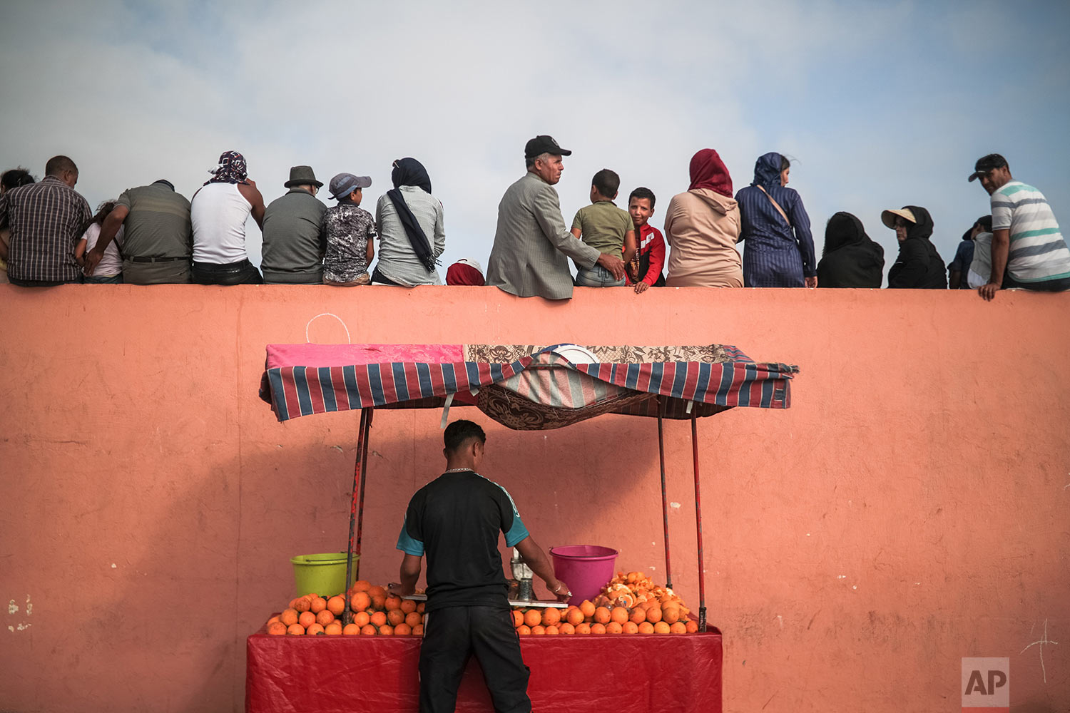 A vendor sells orange juice as people sit on a fence to watch a horsemanship show known as Fantasia or Tabourida, in the coastal town of El Jadida, Morocco, July 25, 2019. (AP Photo/Mosa'ab Elshamy)