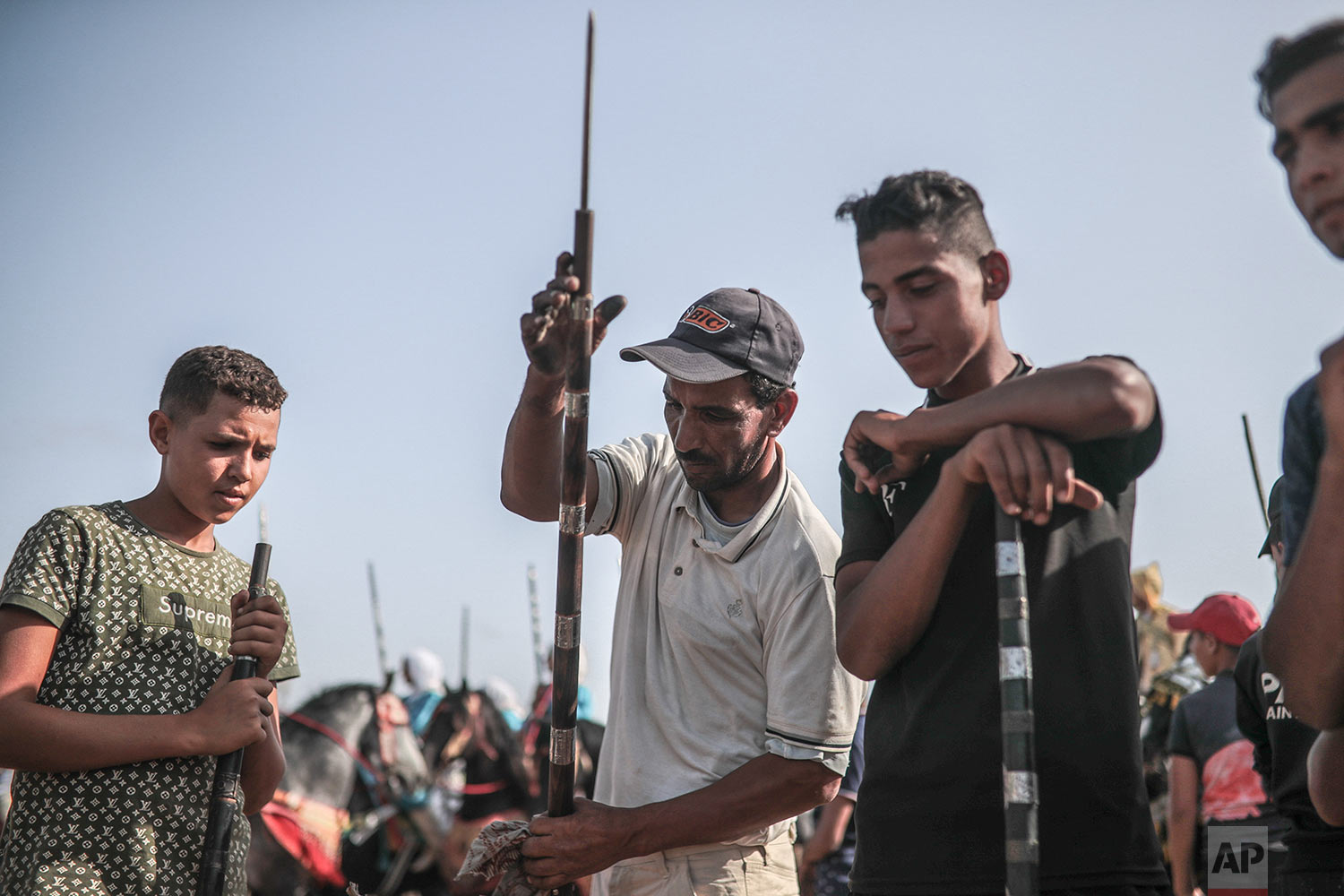 A man helps prepare rifles before being loaded with gunpowder to be used in Tabourida in the coastal town of El Jadida, Morocco, July 25, 2019. (AP Photo/Mosa'ab Elshamy)