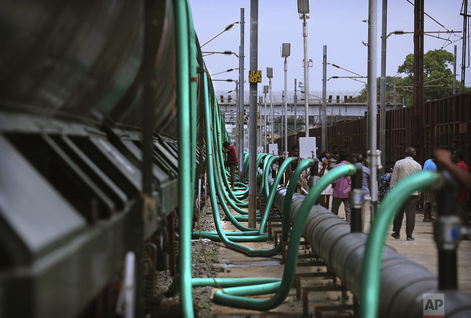 Hundreds of hose-pipes are used to fill wagons of a train with drinking water piped through from the Mettur dam on the Cauvery River at Jolarpet railway station, 216 kilometers (135 miles) from Chennai in Southern Indian state of Tamil Nadu, Wednesday, July 17, 2019. (AP Photo/Manish Swarup)