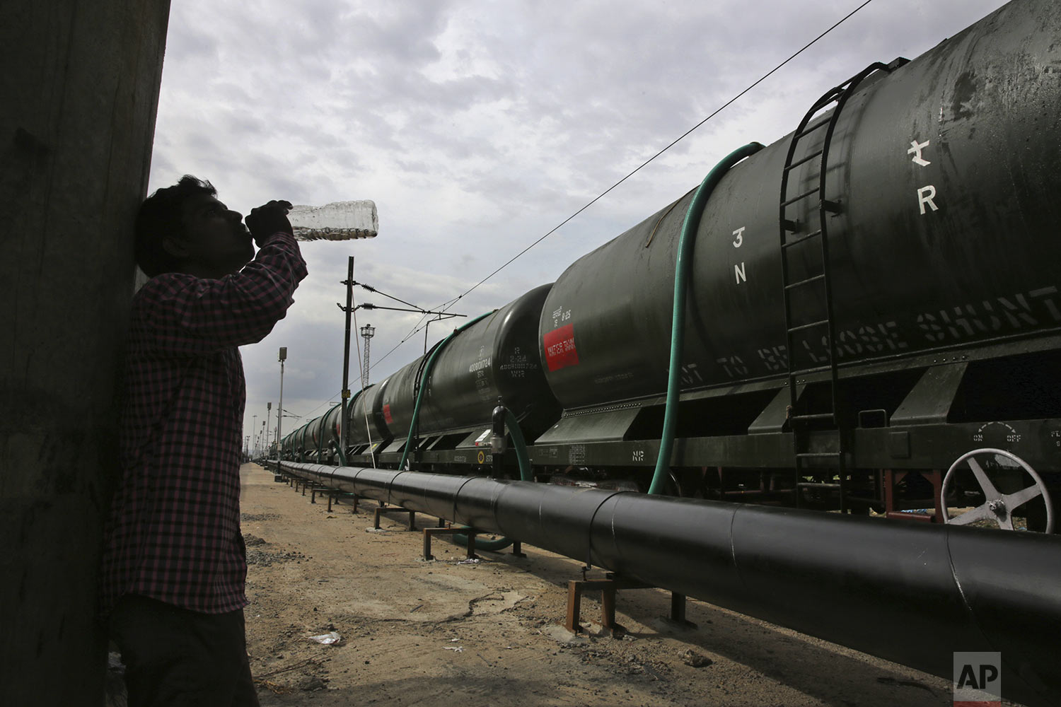 A worker takes a break to drink water while hundreds of hose-pipes are used to fill wagons of a train with drinking water piped through the Mettur dam on the Cauvery River at Jolarpet railway station, 216 kilometers (135 miles) from Chennai in Southern Indian state of Tamil Nadu, Wednesday, July 17, 2019. (AP Photo/Manish Swarup)