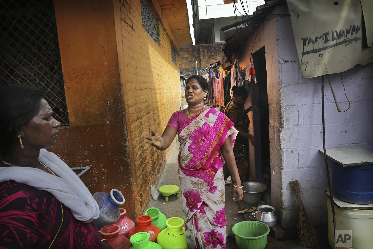 K.Devi, center, talks to her neighbor as they wait for water truck to arrive in their shanty town in Chennai in Southern Indian state of Tamil Nadu, Thursday, July 18, 2019. (AP Photo/Manish Swarup)