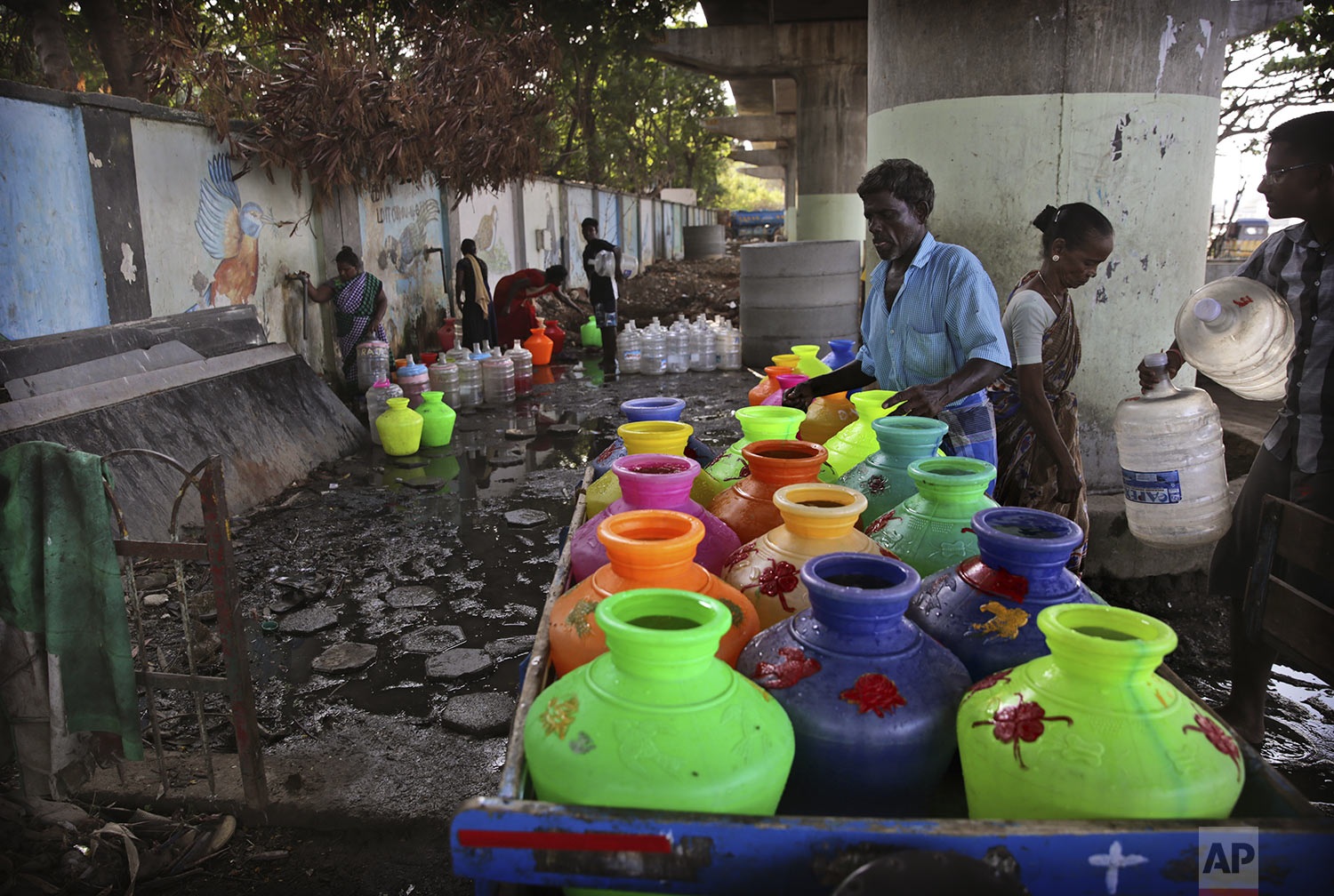 Indians fill drinking water from the taps of water filling depot in Chennai in Southern Indian state of Tamil Nadu, Monday, July 15, 2019. (AP Photo/Manish Swarup)