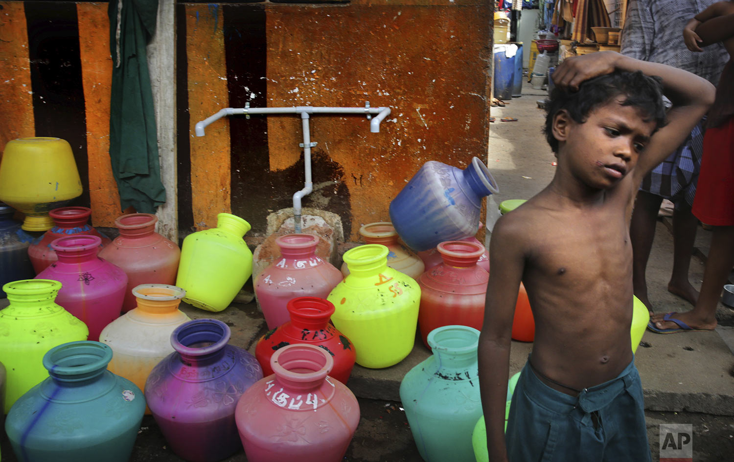 A boy waits at water assembly point in a locality in Chennai in Southern Indian state of Tamil Nadu, Thursday, July 18, 2019, photo. (AP Photo/Manish Swarup)