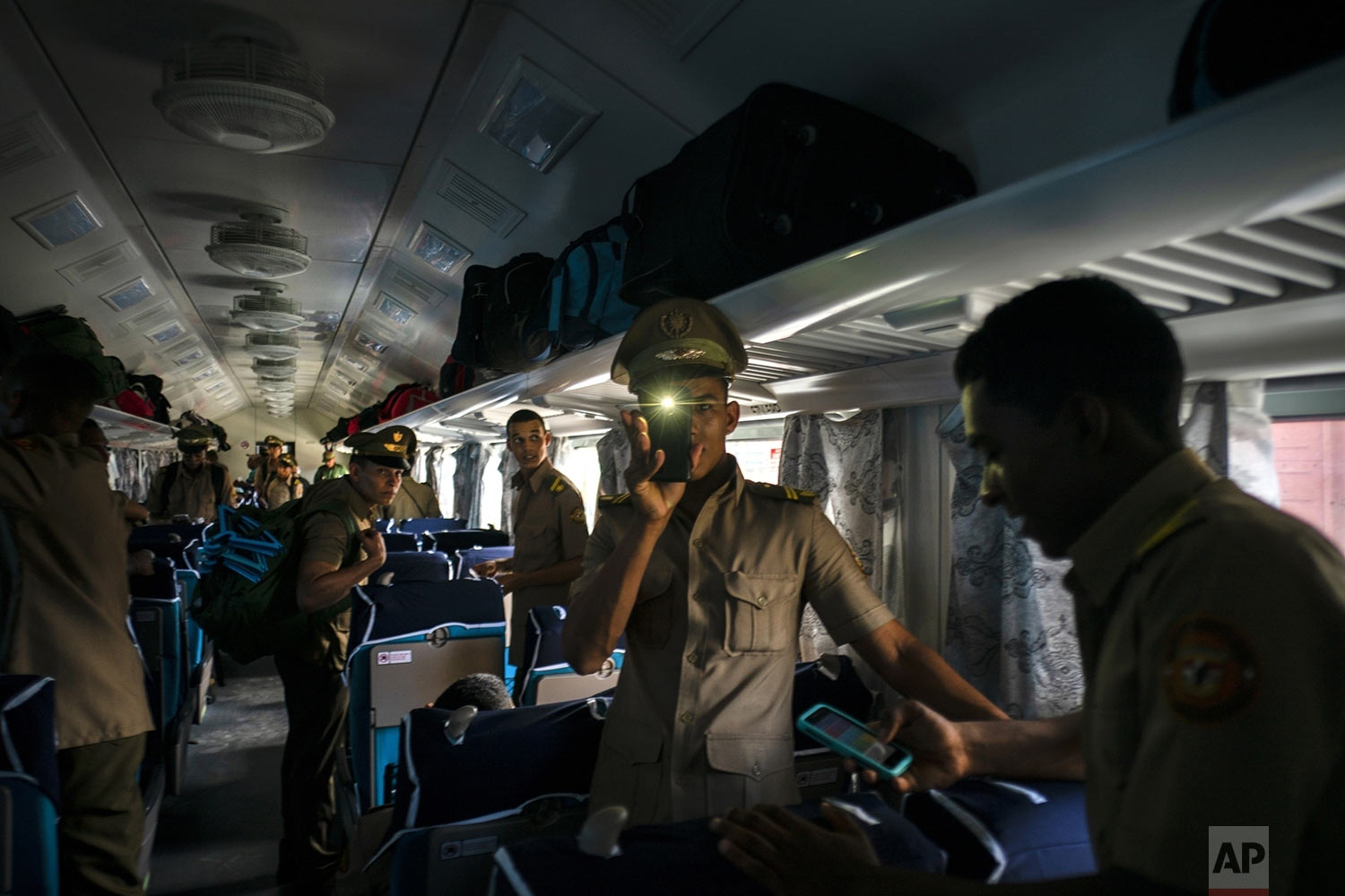Cuban cadets board the first train using new equipment from China, in Havana, Cuba, Saturday, July 13, 2019. The first train using new equipment from China pulled out of Havana Saturday, hauling passengers on the start of a 915-kilometer (516-mile) journey to the eastern end of the island as the government tries to overhaul the country's aging and decrepit rail system. (AP Photo/Ramon Espinosa)