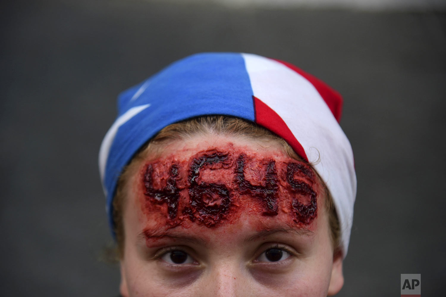Nicole Diaz wears special effects make-up with hurricane Maria's death toll number written on her forehead, while protesting against Governor Ricardo Rossello, in San Juan, Puerto Rico, July 19, 2019. Protesters are demanding Rossello step down for his involvement in a private chat in which he used profanities to describe an ex-New York City councilwoman and a federal control board overseeing the island's finance. (AP Photo/Carlos Giusti)