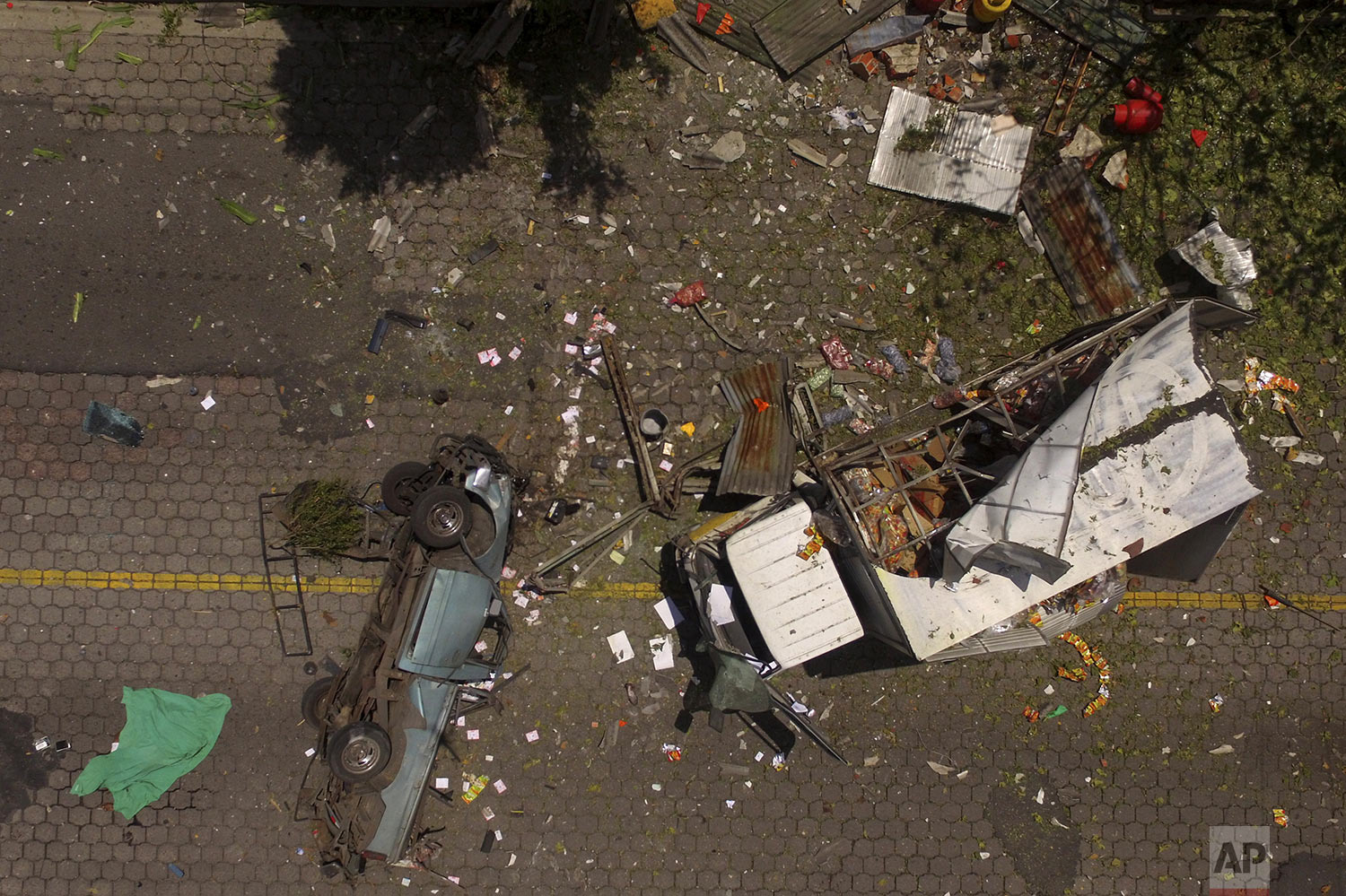 Trucks and debris lie scattered after a deadly explosion of propane gas cylinders at a depot in Mejicanos, El Salvador, Friday, July 12, 2019. Defense Minister Rene Merino visiting the site said that early indications suggested the explosion was accidental, but that authorities are still investigating any possible connection to terrorism by the gangs. (AP Photo/Salvador Melendez)