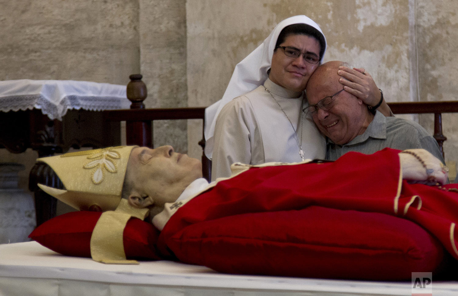 Reynol Alamino Ortega cries next to the body of his cousin, Cardinal Jaime Lucas Ortega y Alamino, during his wake inside the Cathedral in Havana, Cuba, Saturday, July 27, 2019. Ortega, a sugar worker's son who oversaw the first papal visit to Cuba, helped lower barriers to believers in the communist country and played a role in mediating improved U.S.-Cuba ties, died Friday at age 82. (AP Photo/Ismael Francisco)