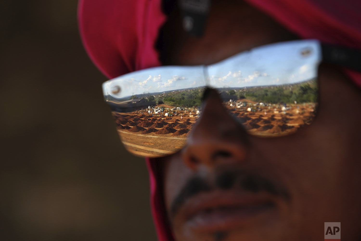 The graves where a number of inmates that where killed in a recent prison riot are to buried, are reflected on the sun glasses of a cemetery employee, in Altamira, Para state, Brazil, Thursday, Aug. 1, 2019. At least 58 prisoners were killed by other inmates during clashes between organized crime groups in the Altamira prison in northern Brazil Monday with 16 of the victims being decapitated, according to prison officials. (AP Photo/Raimundo Pacco)