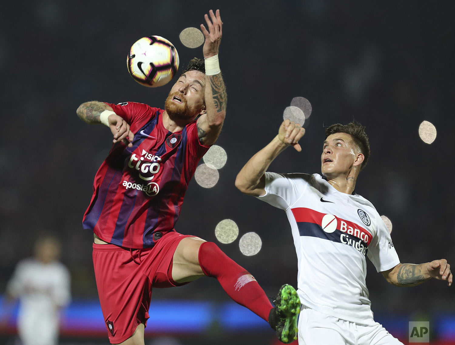 Gaston Reniero of Argentina's San Lorenzo, right, fights for the ball with Fernando Amorebieta of Paraguay's Cerro Porteno during a Copa Libertadores soccer game in Asuncion, Paraguay, Wednesday, July 31, 2019. (AP Photo/Jorge Saenz)