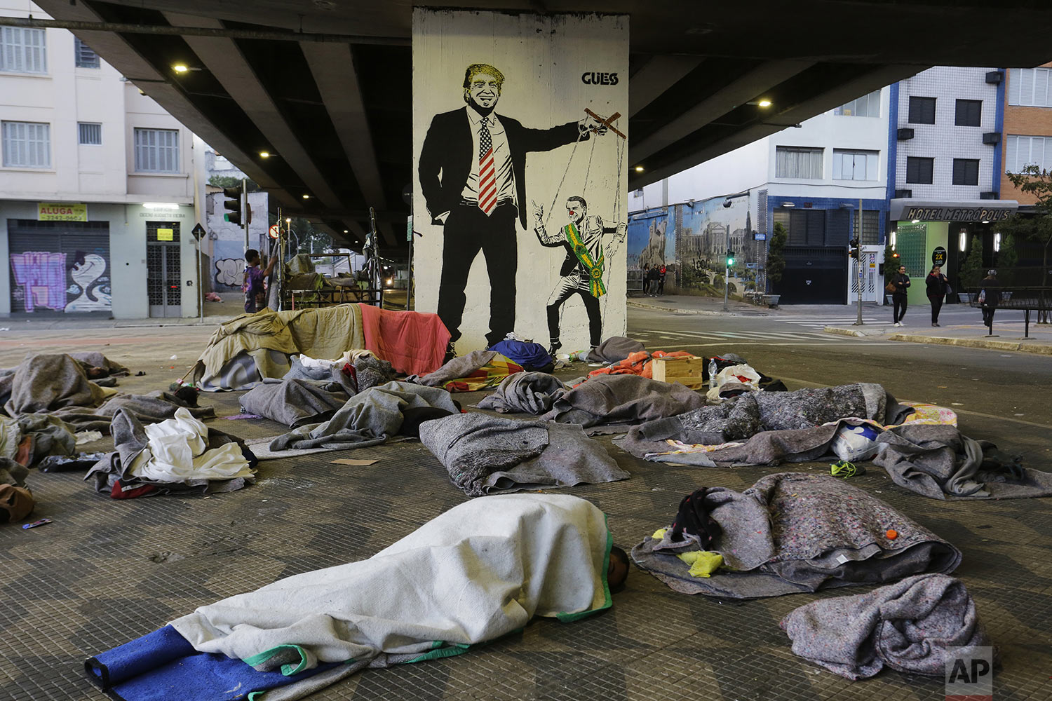 "Homeless people sleep under a bridge in front of a mural depicting U.S. President Donald Trump as a puppeteer manipulating Brazil's President Jair Bolsonaro, in downtown Sao Paulo, Brazil, Tuesday, July 23, 2019.  Bolsonaro said last week that severe hunger is not a problem for the country. He acknowledged that things could ""go bad"" and people might ""not eat well."" But, he added: ""To speak of starving in Brazil is a big lie."" (AP Photo/Nelson Antoine)"