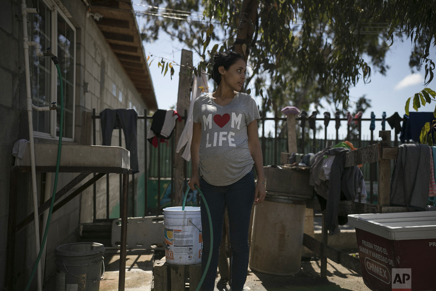 In this May 23, 2019 photo, pregnant teen migrant Milagro de Jesus Henriquez Ayala fills a bucket with water at the Agape World Mission shelter in Tijuana, Mexico. (AP Photo/Emilio Espejel)