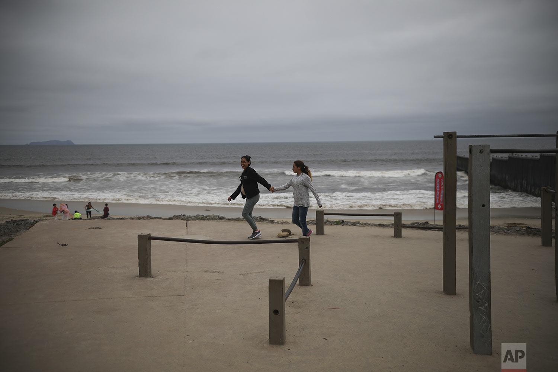 In this June 05, 2019 photo, teen sisters Milagro de Jesus Henriquez Ayala and Xiomara Enriquez play in the exercise area of Playas de Tijuana, Mexico. (AP Photo/Emilio Espejel)