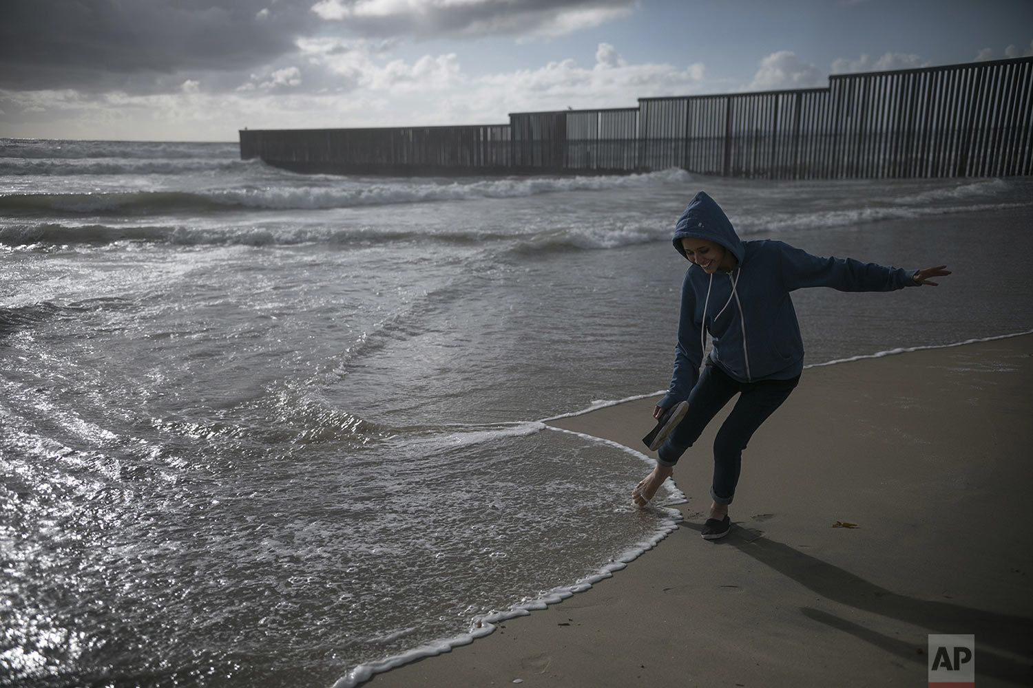 In this May 20, 2019 photo, teen migrant Milagro de Jesus Henriquez Ayala dips her foot in the Pacific Ocean, just a few meters from the border wall that separates Mexico from the United States, at Playas de Tijuana, Mexico. (AP Photo/Emilio Espejel)