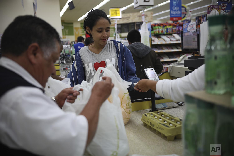 In this May 23, 2019 photo, Salvadoran teen migrant Milagro de Jesus Henriquez Ayala, goes shopping at a supermarket in Tijuana, Mexico. (AP Photo/Emilio Espejel)