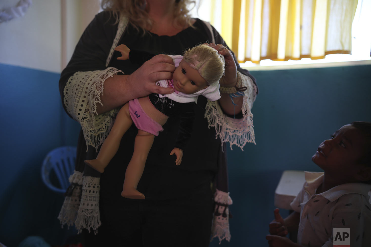 In this May 25, 2019 photo, Mindi Parish Stainer holds a doll during the baby shower for Salvadoran teen migrant Milagro de Jesus Henriquez Ayala, at a meeting hall in Tijuana, Mexico. Parish Stainer has been instrumental in getting the help the pregnant teenager Milagro Henriquez Ayala needed to bring her baby to term. (AP Photo/Emilio Espejel)
