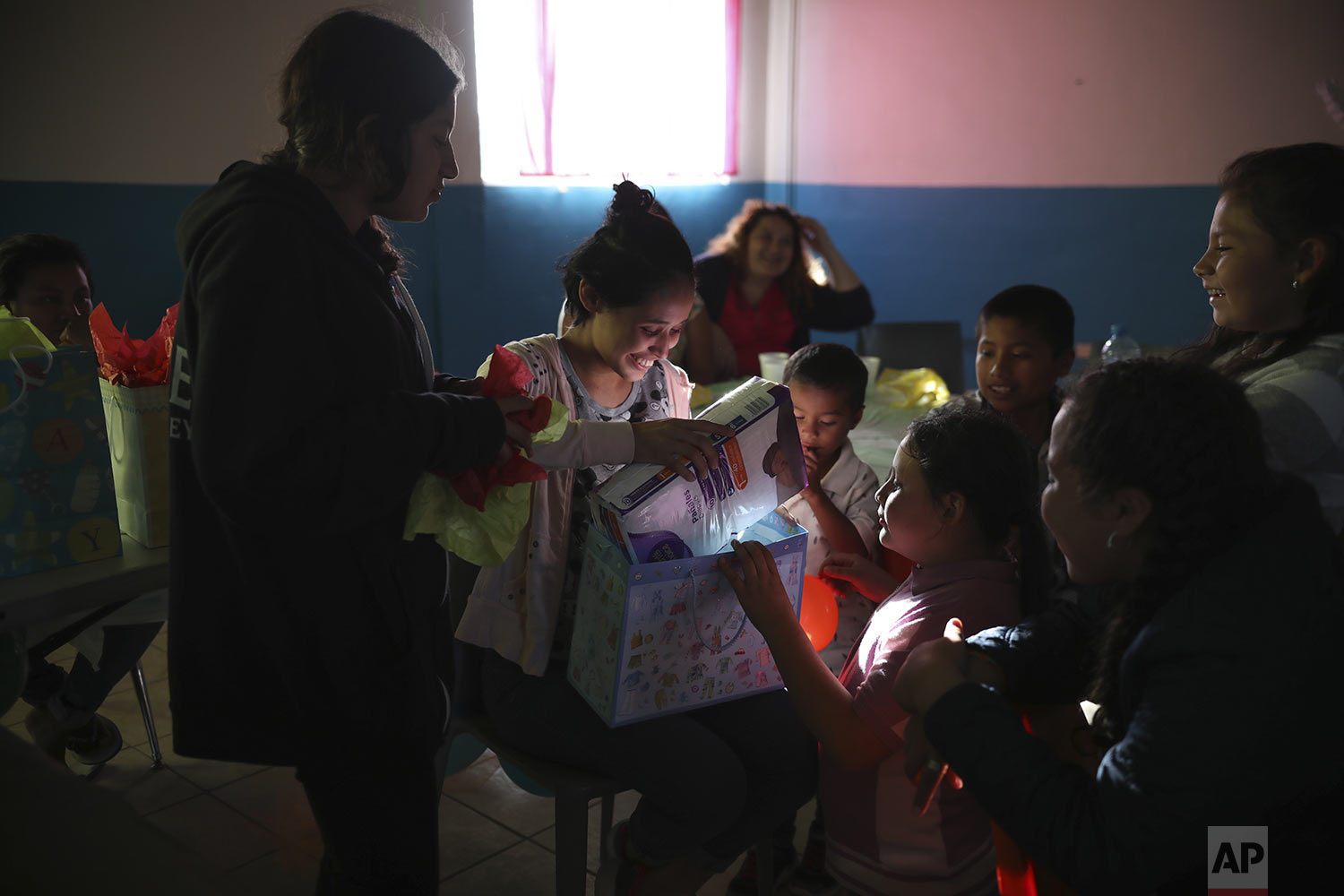 In this May 25, 2019 photo, Salvadoran teen migrant Milagro de Jesus Henriquez Ayala, opens her gifts during her baby shower at at a meeting hall in Tijuana, Mexico.  (AP Photo/Emilio Espejel)