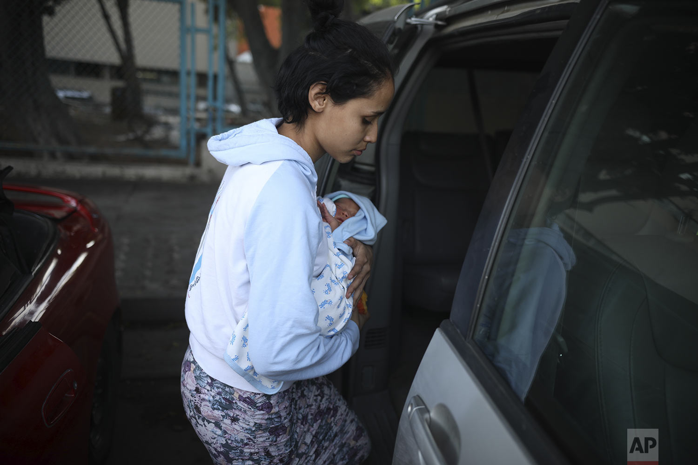 In this June 10, 2019 photo, Salvadoran teen migrant Milagro de Jesus Henriquez Ayala carries her newborn son Alexander, as she boards Rev. Albert Rivera's car, outside the Tijuana General Hospital in Mexico.  (AP Photo/Emilio Espejel)