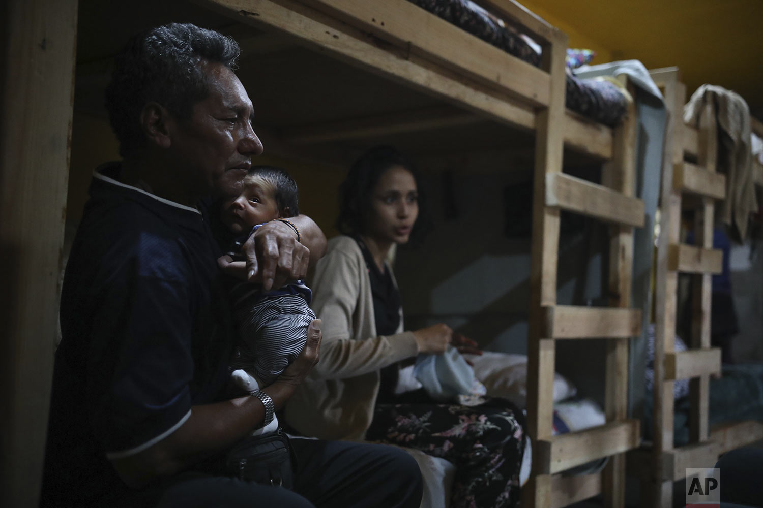In this June 15, 2019 photo, Manuel Henriquez holds his grandson Alexander, as he sits next to his daughter Milagro de Jesus Henriquez Ayala, on her bed, at the Agape World Mission shelter in Tijuana, Mexico. (AP Photo/ Emilio Espejel)