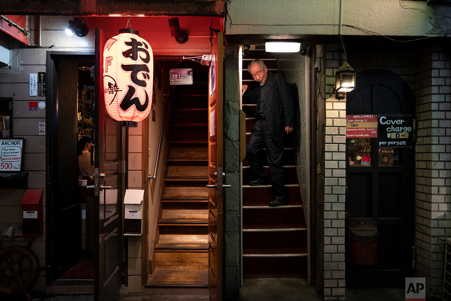 A man walks down the steps of a bar at the Golden Gai in the Shinjuku district of Tokyo, July 17, 2019. (AP Photo/Jae C. Hong)