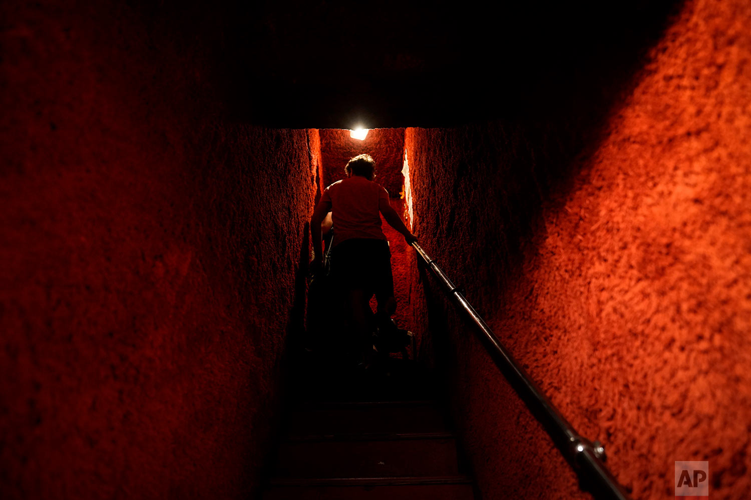 A man walks up a narrow staircase leading to a bar at the Golden Gai in the Shinjuku district of Tokyo, July 26, 2019. (AP Photo/Jae C. Hong)