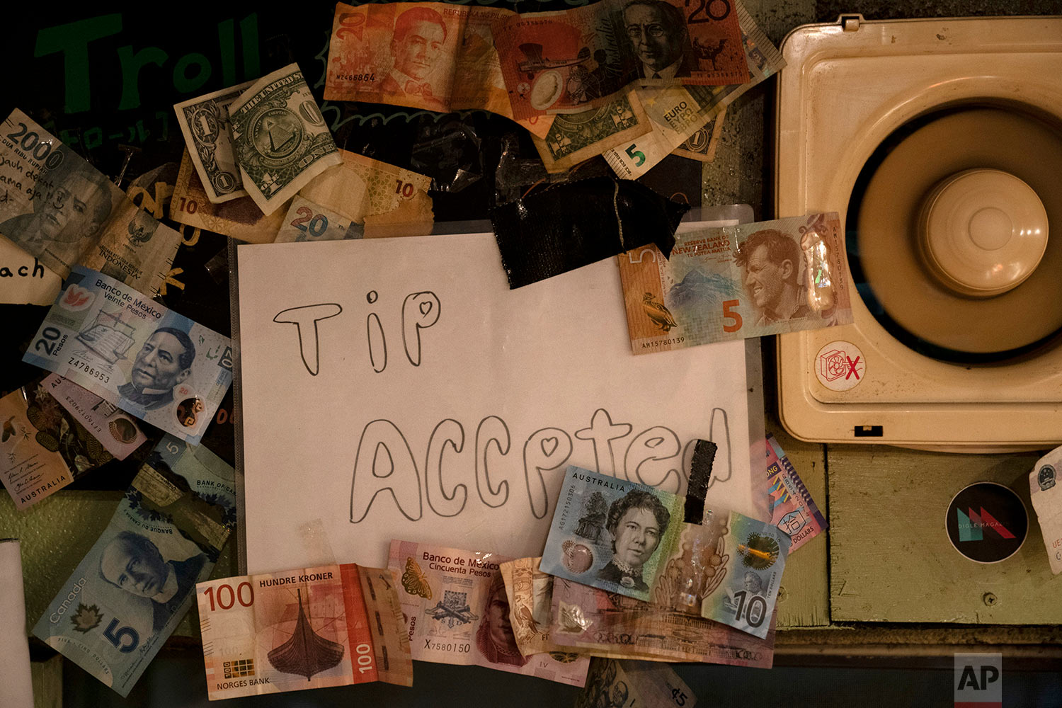 A sign is posted on the wall clustered with bills from various countries in a bar at the Golden Gai in the Shinjuku district of Tokyo, July 17, 2019. (AP Photo/Jae C. Hong)