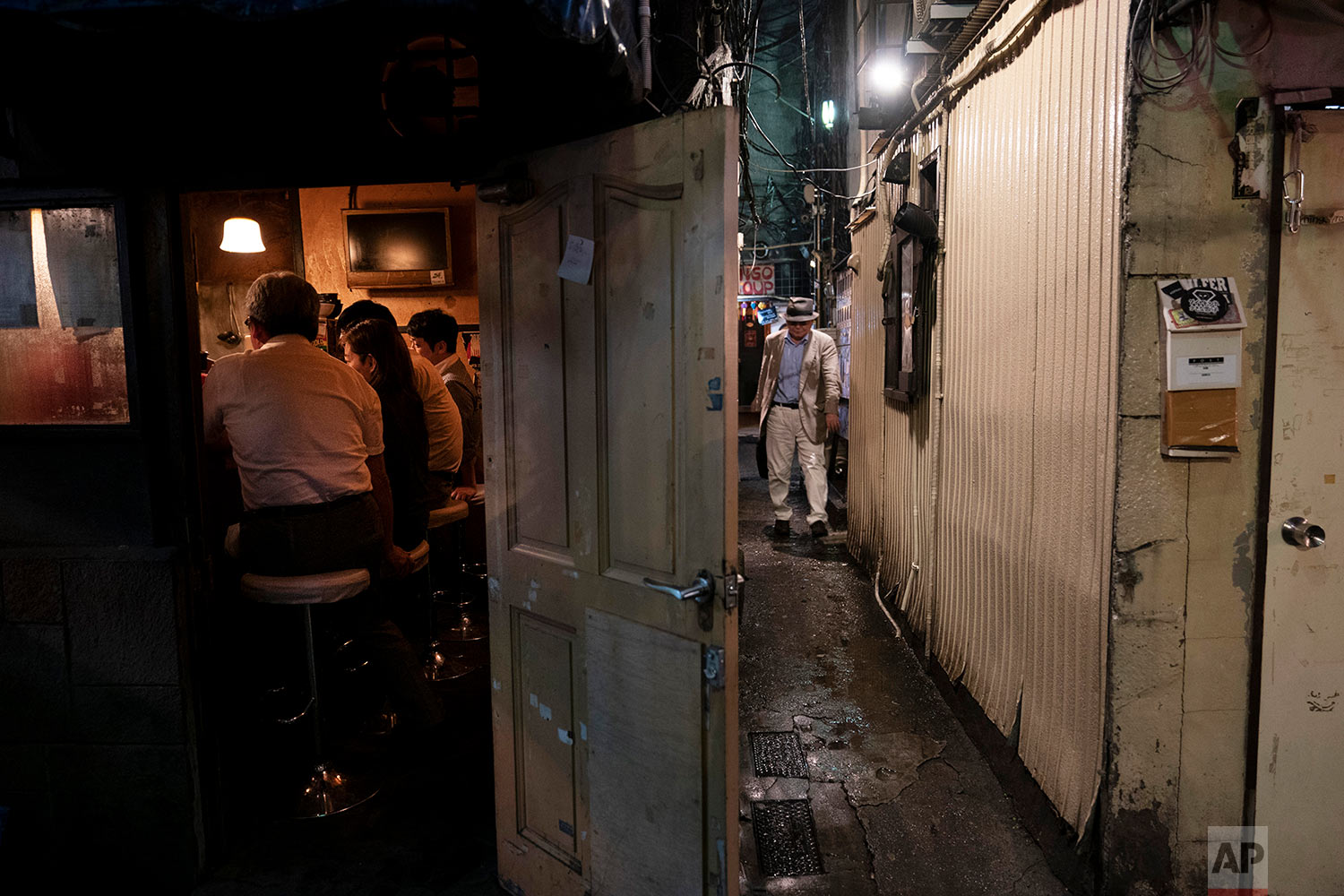 A man makes his way through a narrow passageway between two buildings at the Golden Gai in the Shinjuku district of Tokyo, July 17, 2019. (AP Photo/Jae C. Hong)
