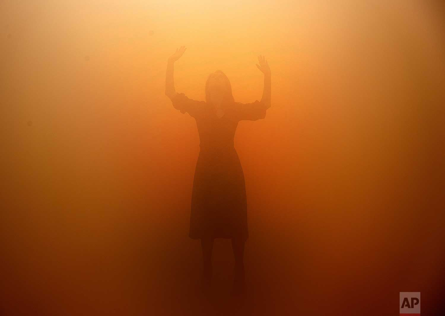 A visitor tries to orientate through a room full of fog called 'Your blind passenger' as part of the exhibition Olafur Eliasson: 'In real life' at the Tate Modern Gallery in London, Tuesday, July 9, 2019. The Tate Modern has brought together around 40 works of Eliasson spanning the last three decades, and are on display from July 11, 2019 until January 5, 2020. (AP Photo/Frank Augstein)