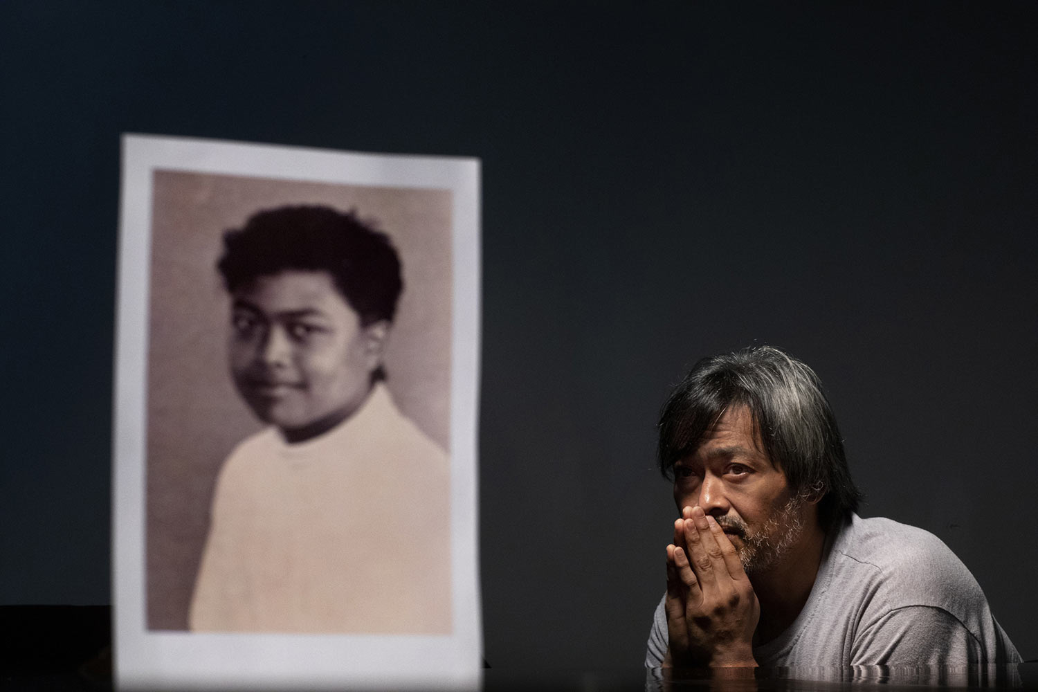 Mark Apuron, 45, sits behind a photo of himself when he was 15 years old. (AP Photo/David Goldman)