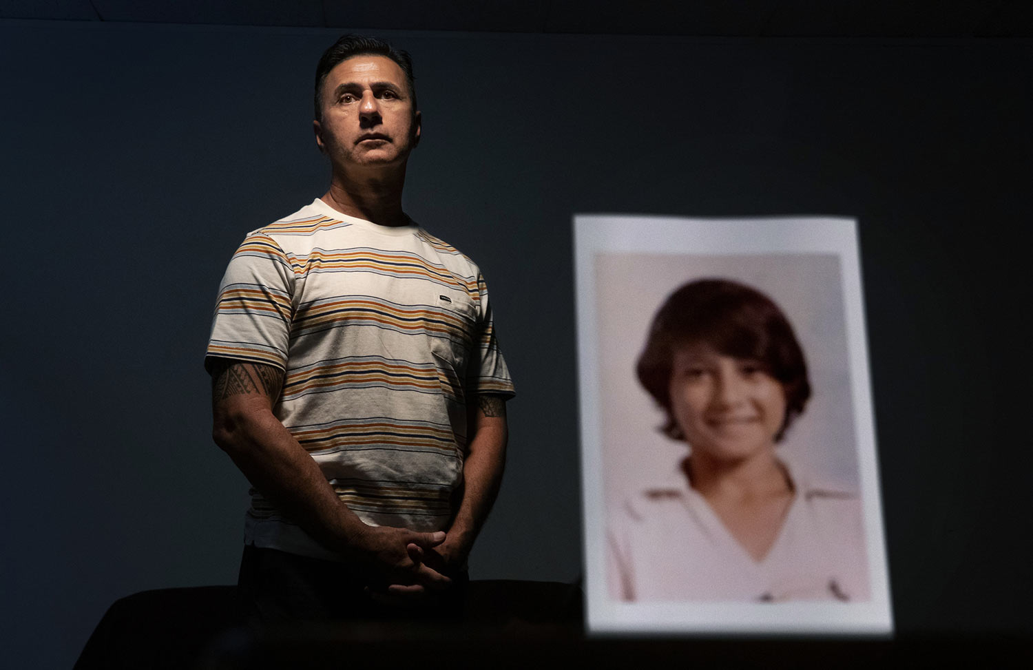 Walter Denton, 55, stands behind a photo of himself when he was about 12 years old. (AP Photo/David Goldman)