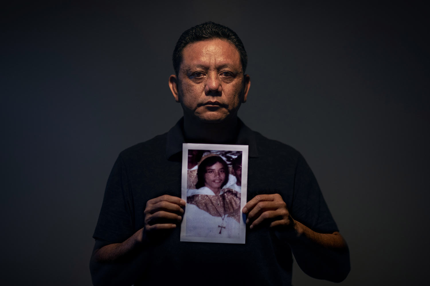 Roland Sondia, 57, holds a photo of himself when he was about 15 years old. (AP Photo/David Goldman)