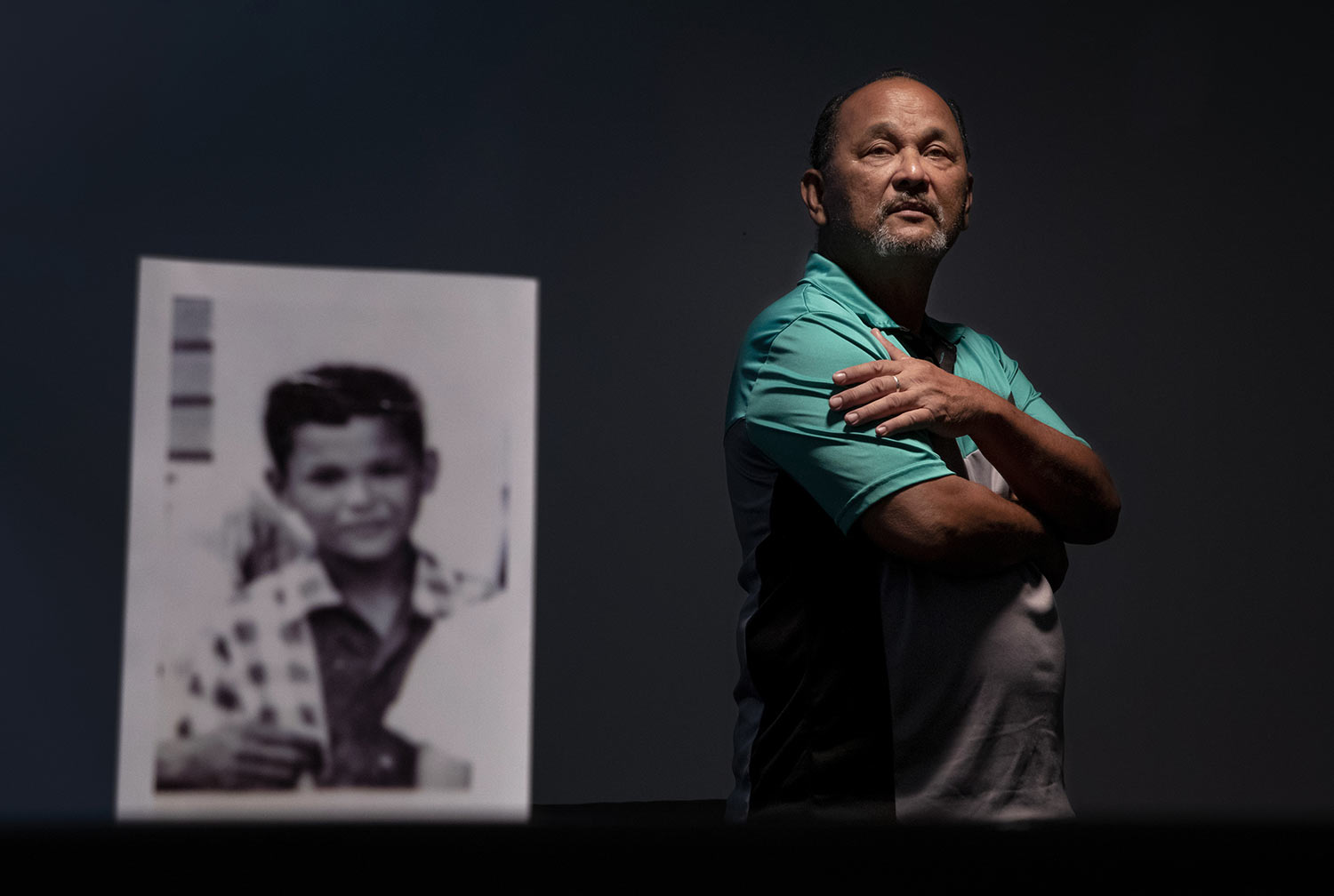 Ramon De Plata, 65, stands behind a photo of himself when he was about 10 years old. (AP Photo/David Goldman)