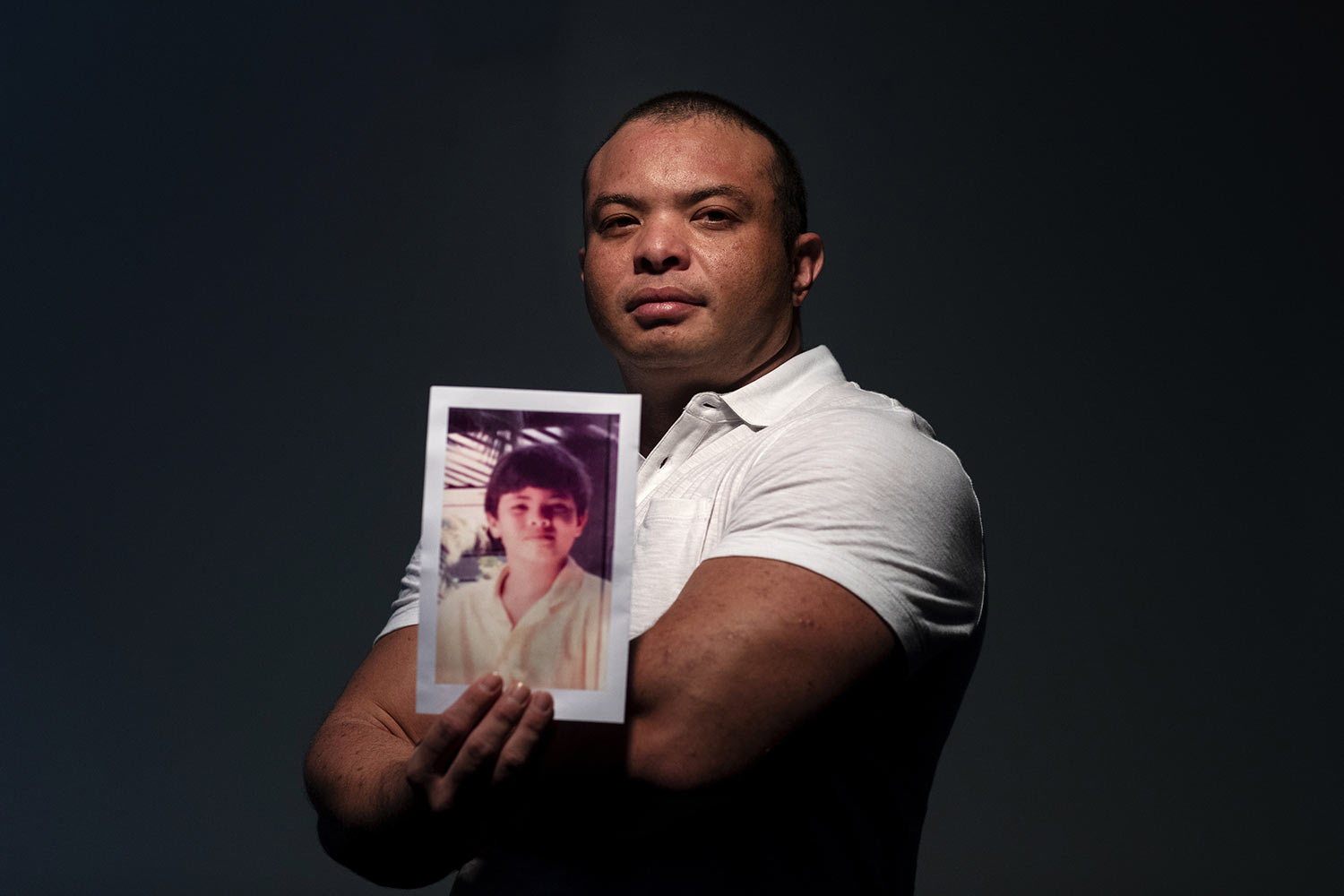 Troy Torres, 38, holds a photo of himself when he was about 12 years old. (AP Photo/David Goldman)