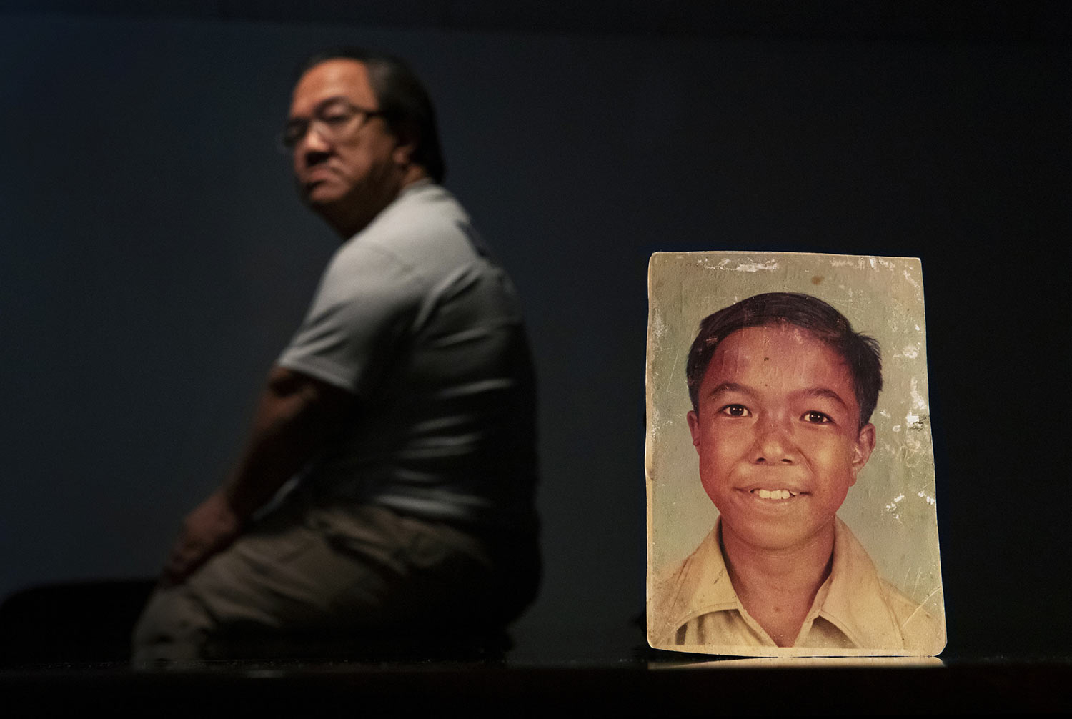 C.M.V., 58, sits behind a photo of himself when he was about 11 years old. (AP Photo/David Goldman)