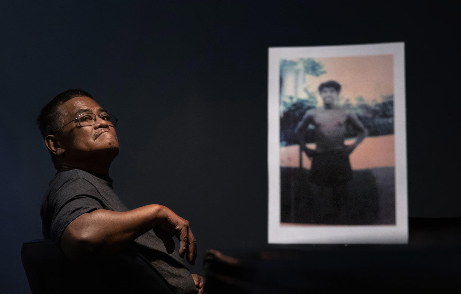Anthony Vegafria, 59, sits behind a photo of himself when he was 13 years old. (AP Photo/David Goldman)