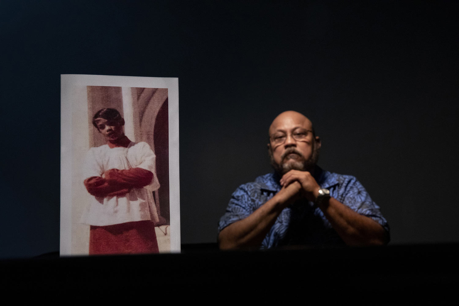 Melvin Duenas, 58, sits beside a photo of himself when he was 11 years old. (AP Photo/David Goldman)