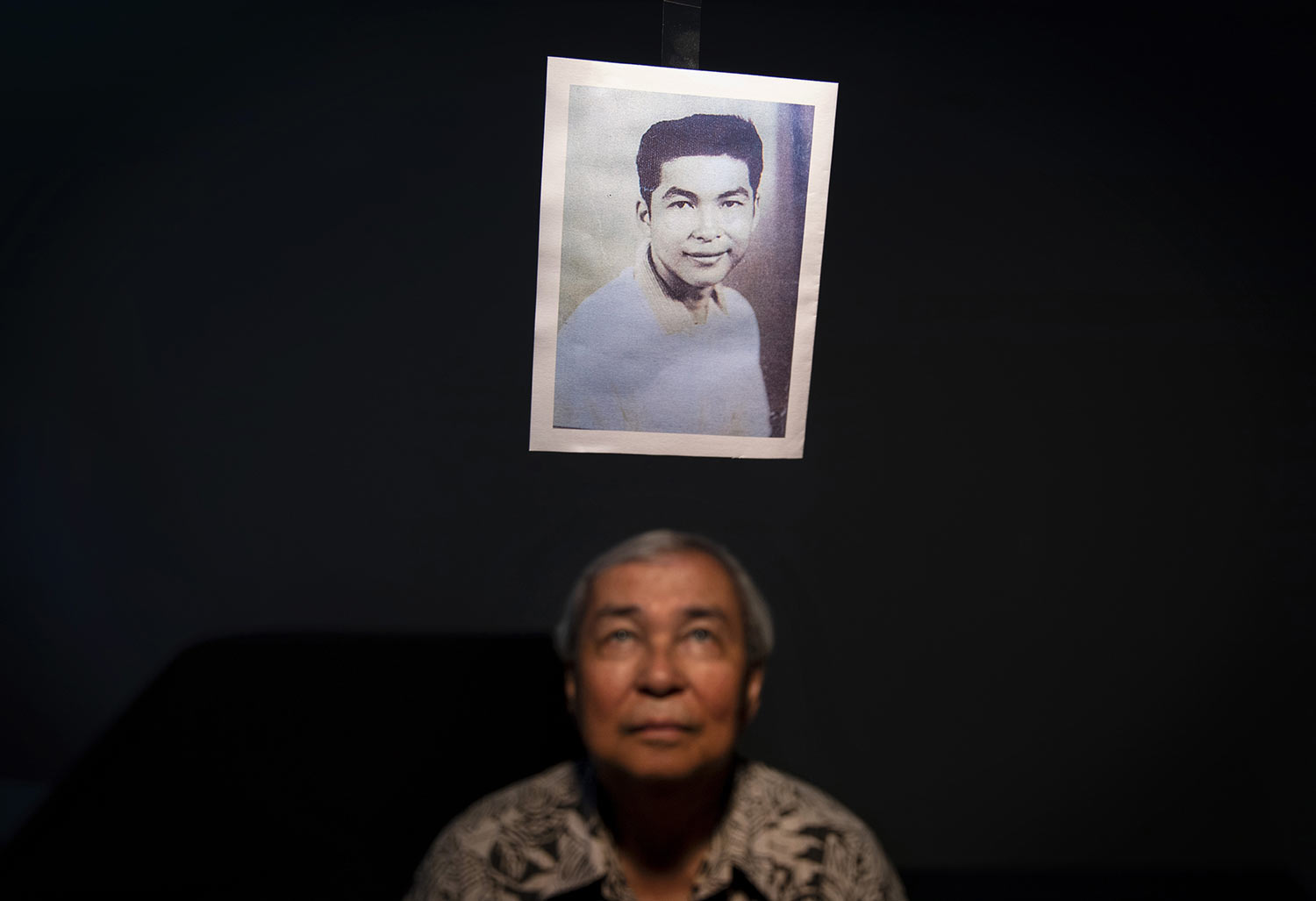 Leo Tudela. 75, looks up at a photo of himself when he was 13 years old. (AP Photo/David Goldman)