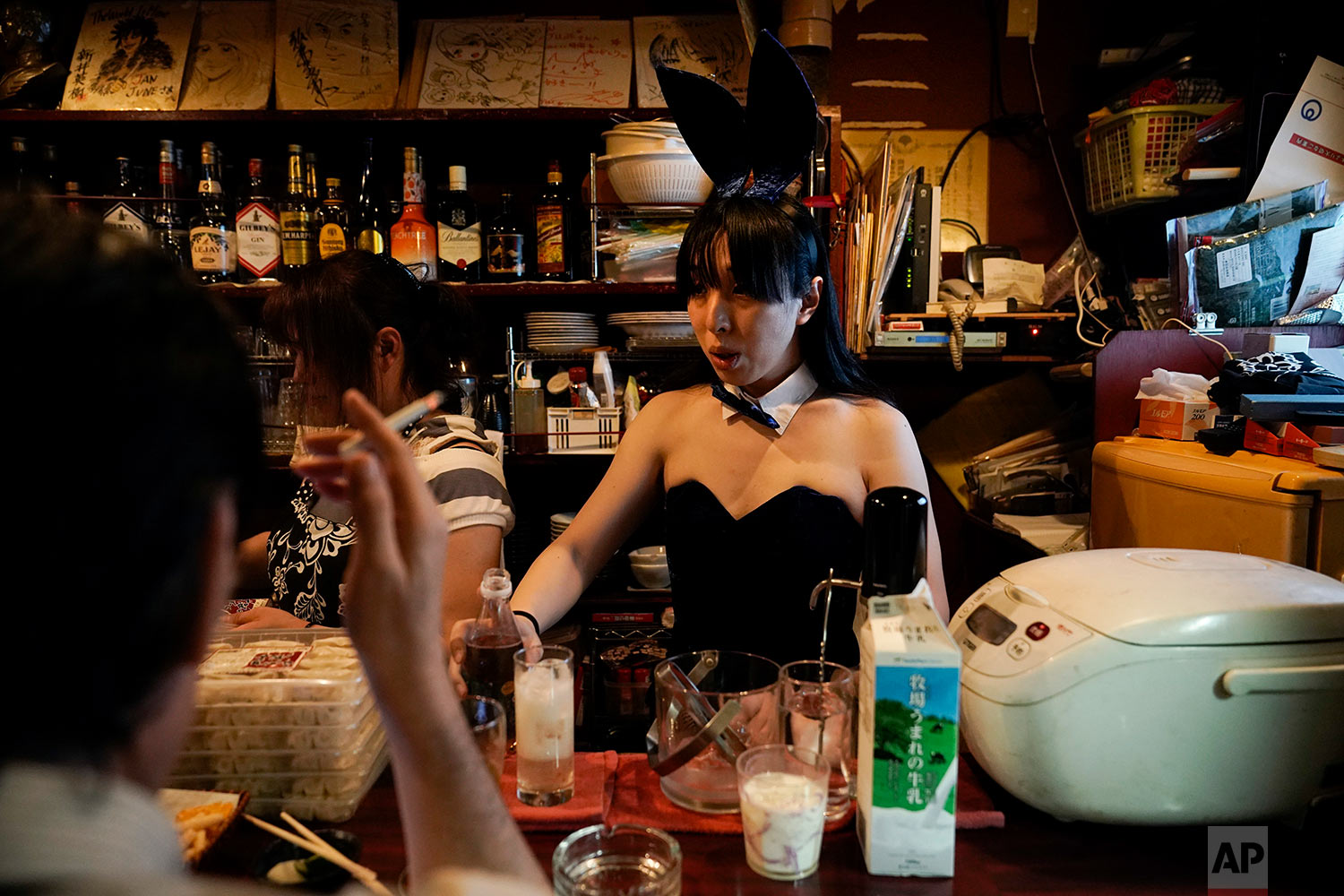 A bartender, in costume, prepares a drink for a patron in a bar at the Golden Gai in the Shinjuku district of Tokyo, July 26, 2019. (AP Photo/Jae C. Hong)