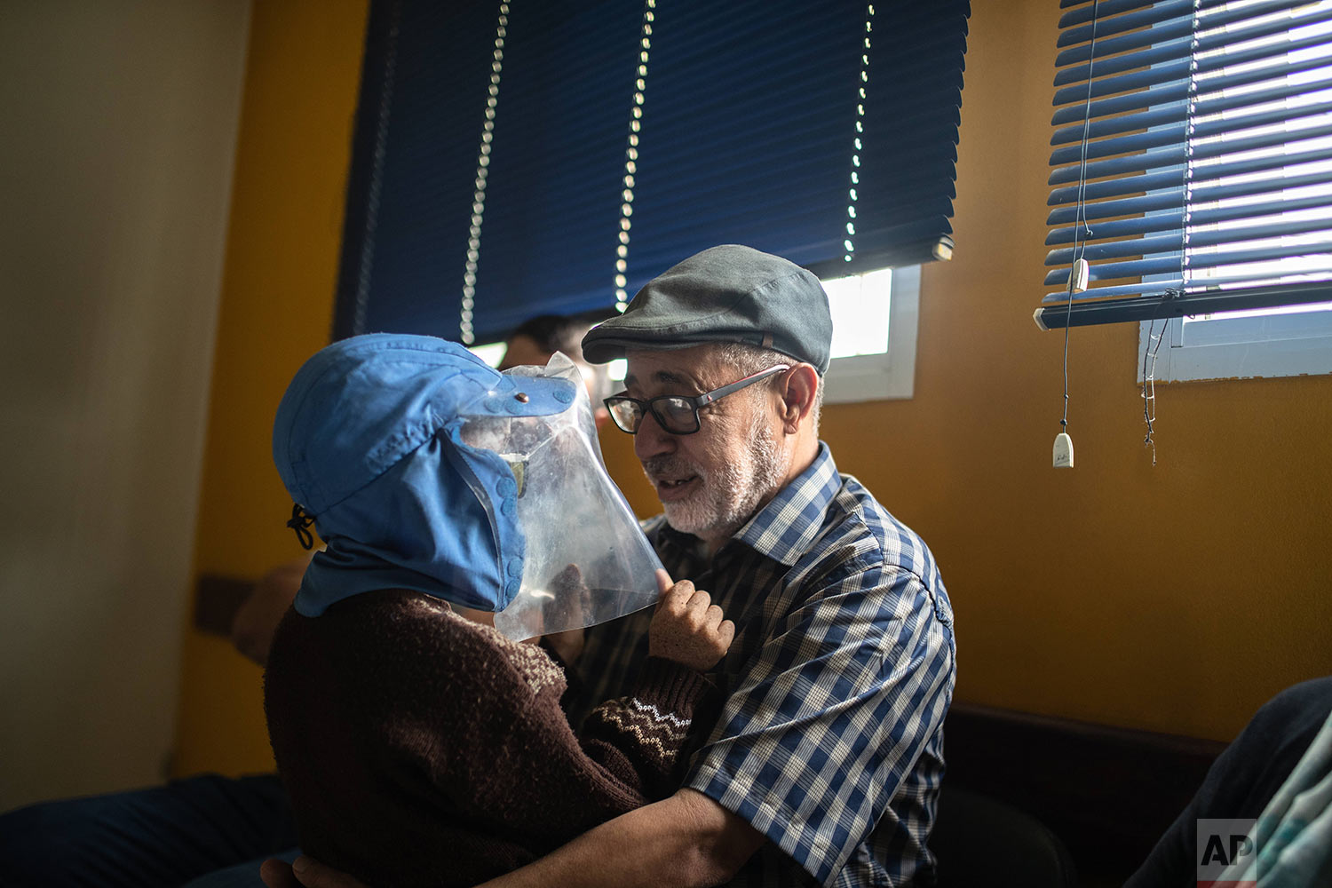 Habib El Ghazaoui, a father who runs the Association for Solidarity with Children of the Moon, plays with 8-year-old Mustapha who is affected by a rare genetic disorder called xeroderma pigmentosum, or XP, inside a hospital in Casablanca, Morocco, July 24, 2019. (AP Photo/Mosa'ab Elshamy)